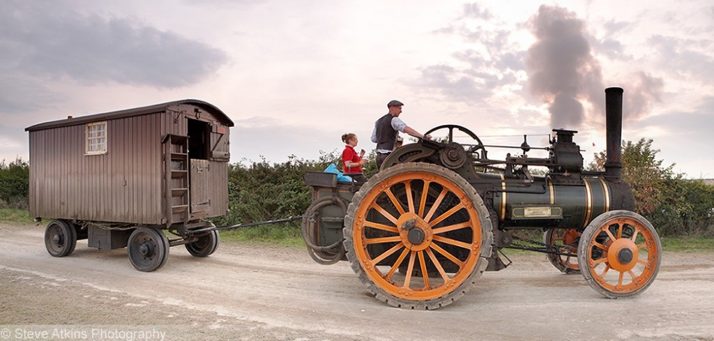 A panoramic image of a steam engine pulling a shepherds hut