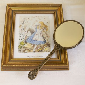 Picture of Alice in Wonderland and a hand held looking glass