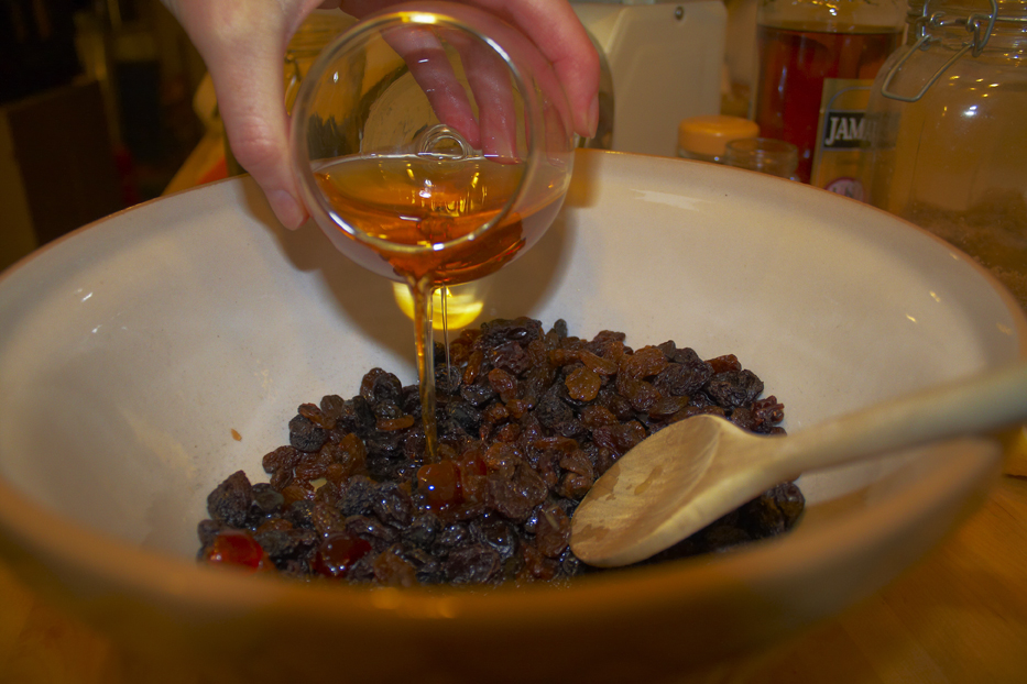 Pouring brandy and rum into the Christmas Cake
