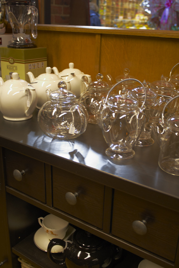 A shelf of glass and porcelain teapots