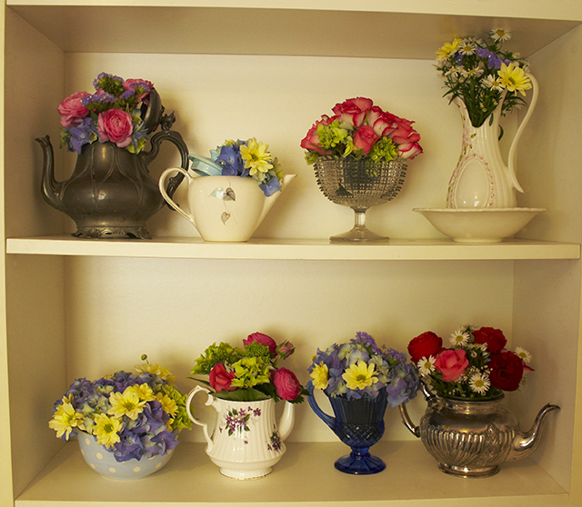 A shelf of flower arrangements in teapots and jugs