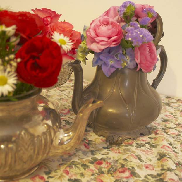 Pink red and blue flowers in a pewter and silver tea pot