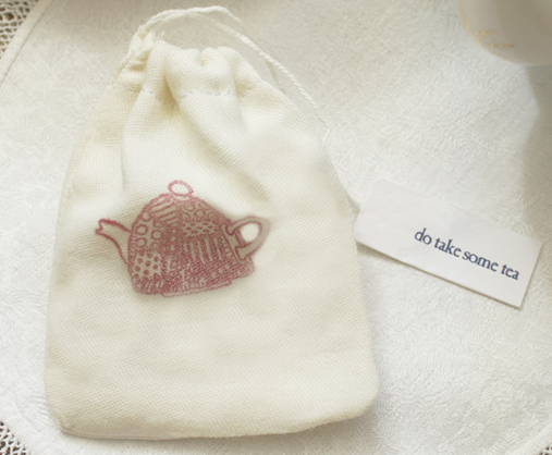 a cotton bag with a red teapot design containing loose leaf tea