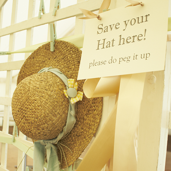 sign for hat saver together with a straw hat pegged onto a trellis