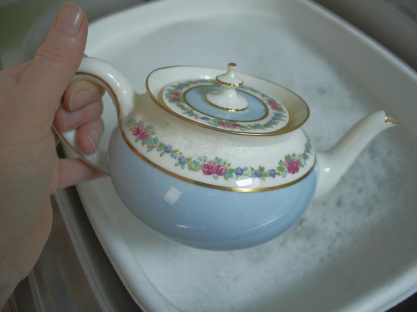 washing a blue vintage teapot