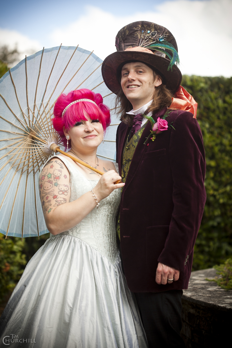 The bride & groom dressed as the queen and hatter