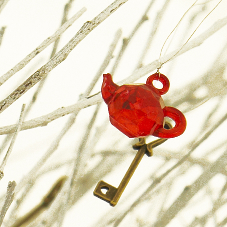 tiny red teapot and key in a white tree